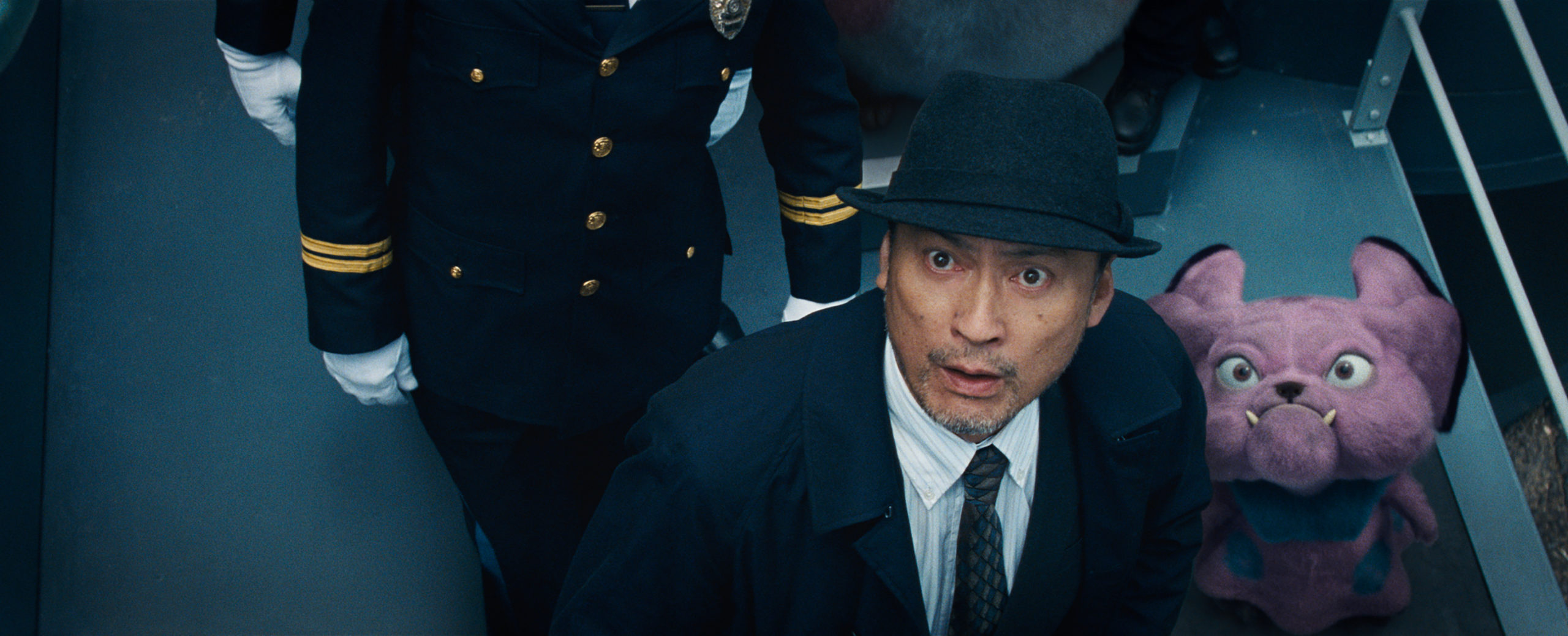 "(L-R) KEN WATANABE as Lieutenant Hide Yoshida and Snubbull in Legendary Pictures' and Warner Bros. Pictures' comedy adventure ""POKÉMON DETECTIVE PIKACHU,"" a Warner Bros. Pictures release."