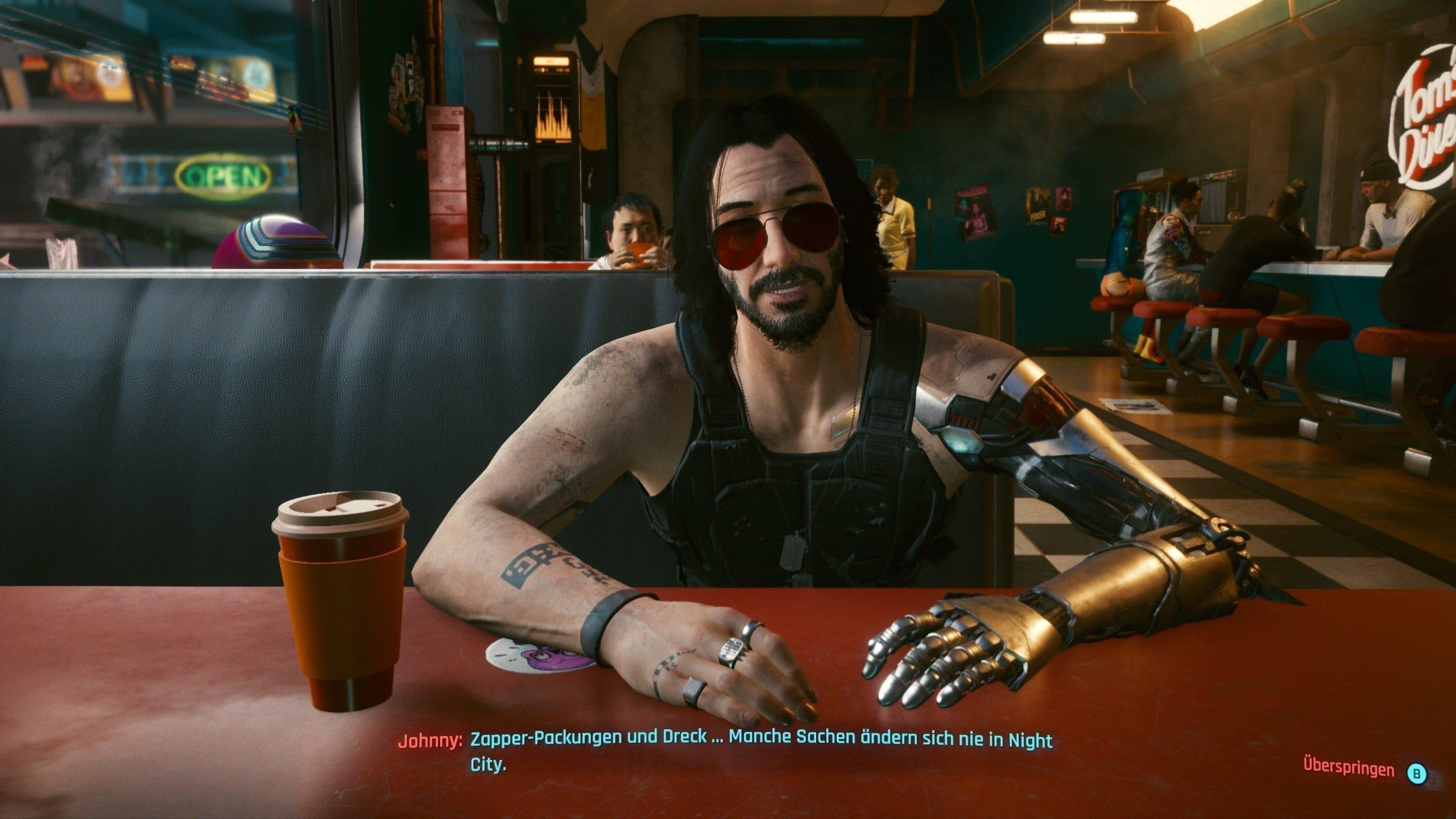 Screenshot von Spiel Cyberpunk 2077 zeigt Johnny Silverhand in einem Diner sitzend